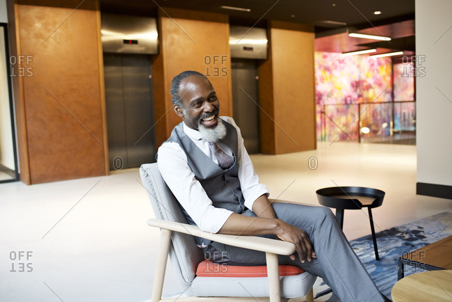 Laughing businessman sitting in a break out area of a modern office