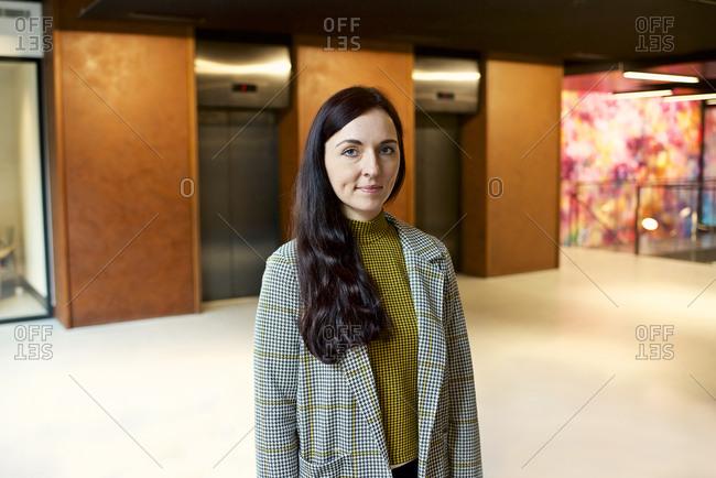 Portrait of a dark-haired businesswoman in a modern office