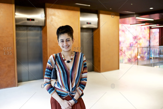 Portrait of a smiling Asian businesswoman inside a modern office