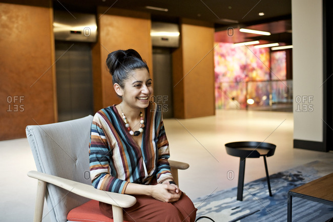 Smiling businesswoman sitting in a break out area of a modern office