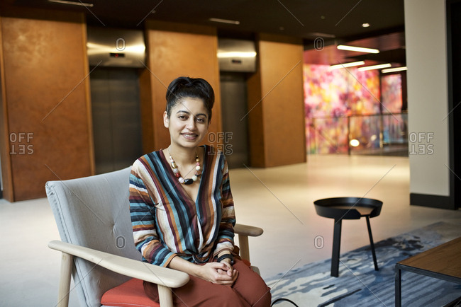 Portrait of an Asian businesswoman sitting in the lobby of a modern office