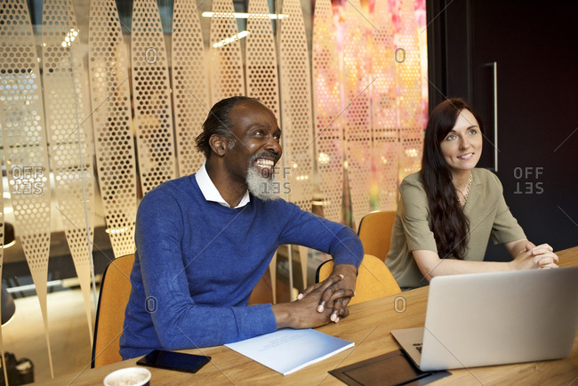 Smiling businesspeople sitting together at a table for a meeting in a contemporary office
