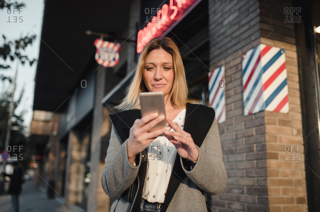 Woman business using her phone in the city