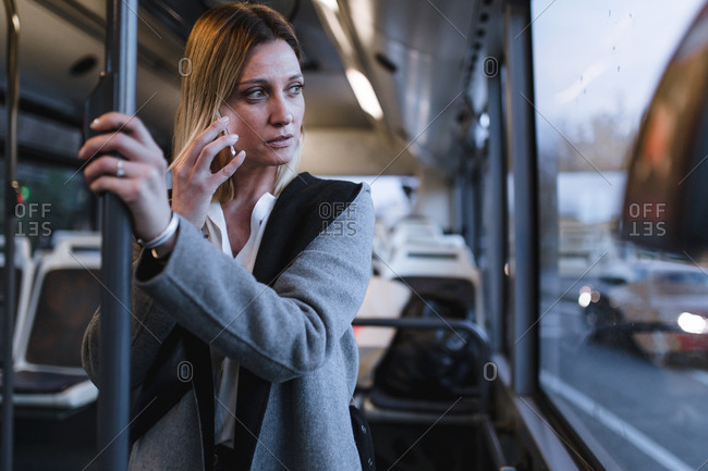 Front view of business blonde woman talking with her phone in a bus