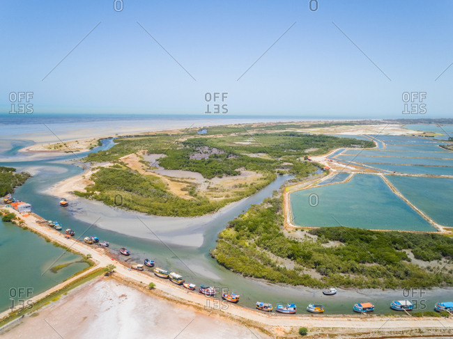 Aerial view of fishing boat group anchored near big salt industry, Brazil.