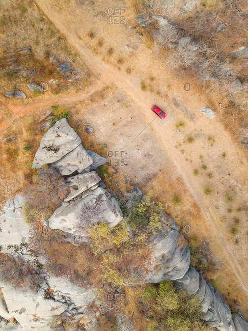 Aerial view of red car parking next to rock formation on arid area, Ceara, Brazil.