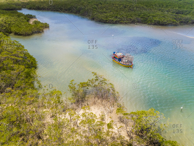 Aerial view of fishing boat navigating on transparent river surrounded by rainforest, Cascalve, Brazil.