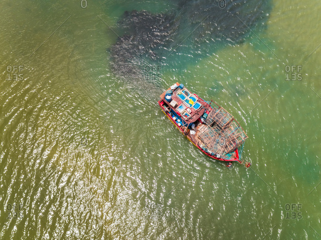 Aerial view of fishing boat navigating on transparent river, Cascalve, Brazil.
