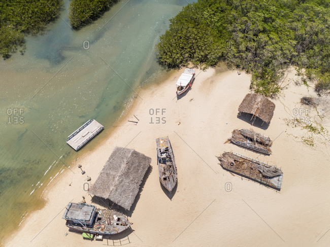 Aerial view of a river bank with simple straw houses and boats, Brazil.