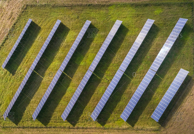 Aerial view above of solar panel rows during daylight, Estonia.