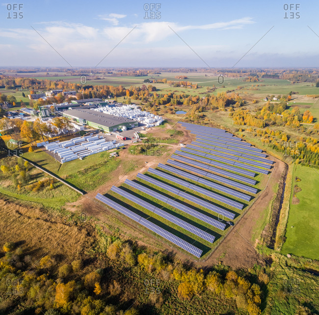 Aerial view of solar panel rows near a forest during Autumn, Estonia.