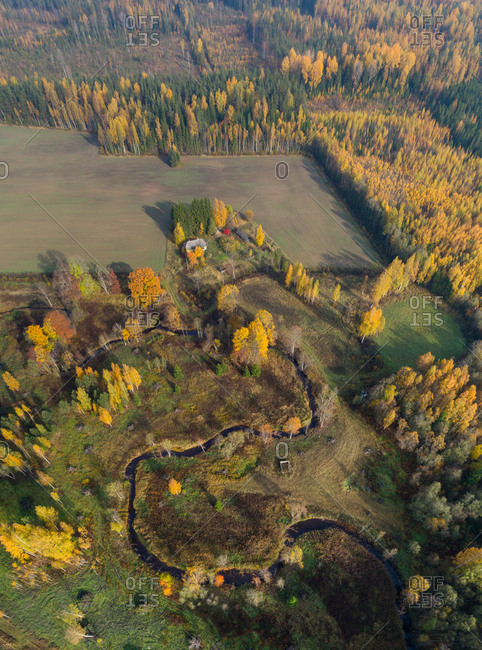 Aerial view of a water stream in a serpentine shape crossing forest, Estonia.
