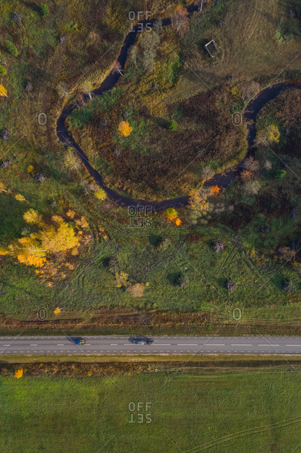 Aerial view above of small river crossing forest near an empty road, Estonia.
