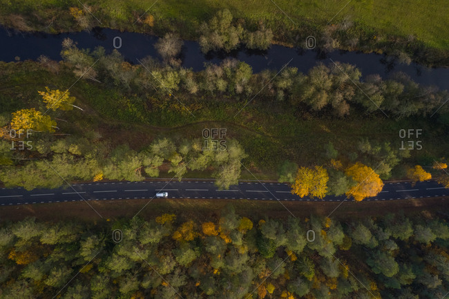 Aerial view above of river crossing forest near an empty road, Estonia.