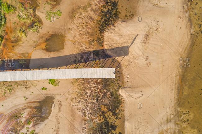 Aerial view of long wood pier above sandy shore, Estonia.