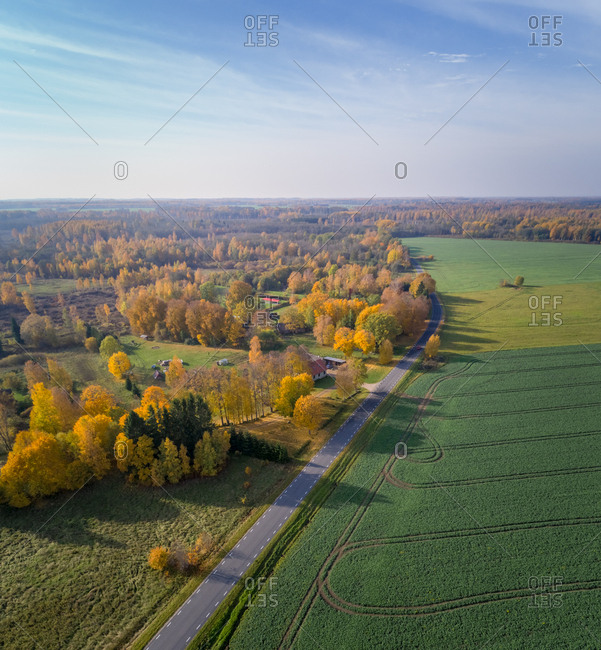 Aerial view of road crossing between agricultural land and village, Estonia.