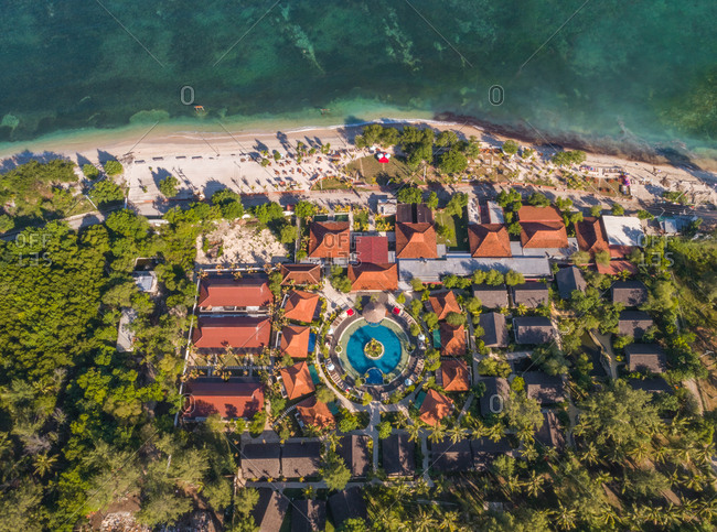 Aerial view above of vacation resort with round pool near the beach, Indonesia.