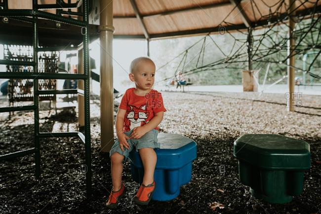 Toddler boy sitting on blue seat on playground