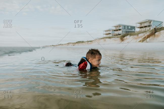 Little boy swimming in ocean with lifejacket