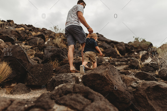 Father and toddler hiking up mountains