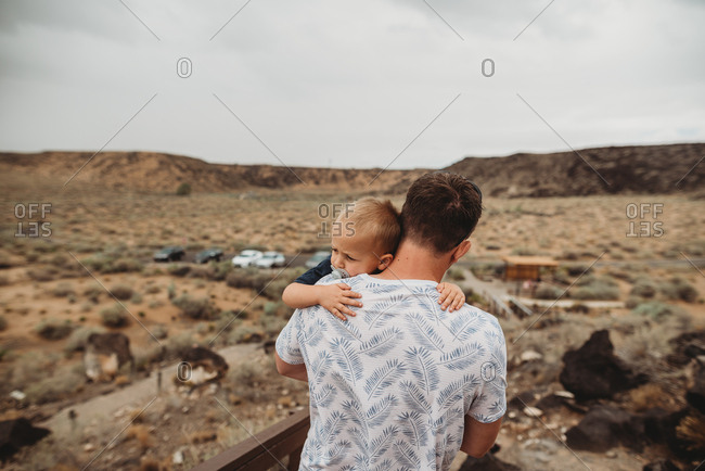 Father carrying toddler while hiking