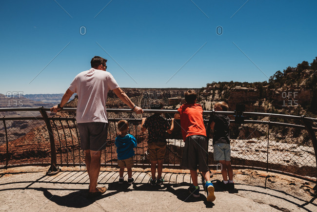 Father and sons looking over fence at Grand Canyon National Park