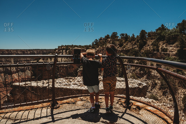 Two boys looking over fence at Grand Canyon National Park