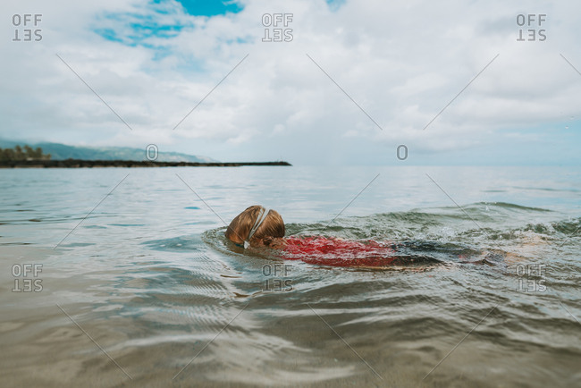 Boy swimming in the ocean off Hawaii