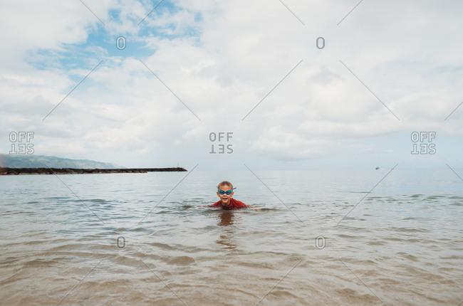 Happy little boy swimming in the ocean off Hawaii