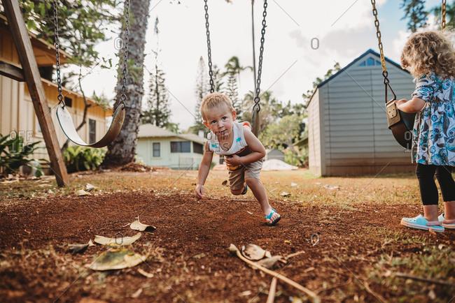 Two kids swinging in backyard