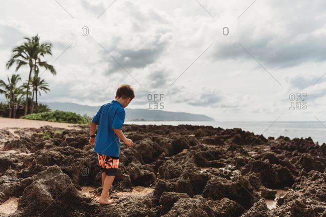 Rear view of boy walking on rocky coast