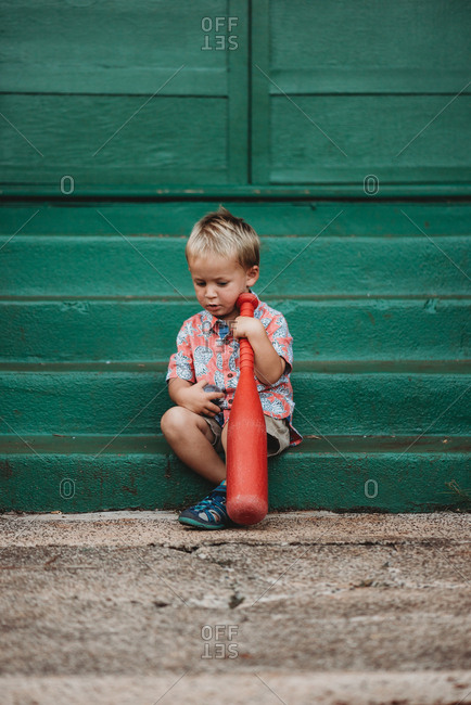 Toddler boy holding a red plastic bat
