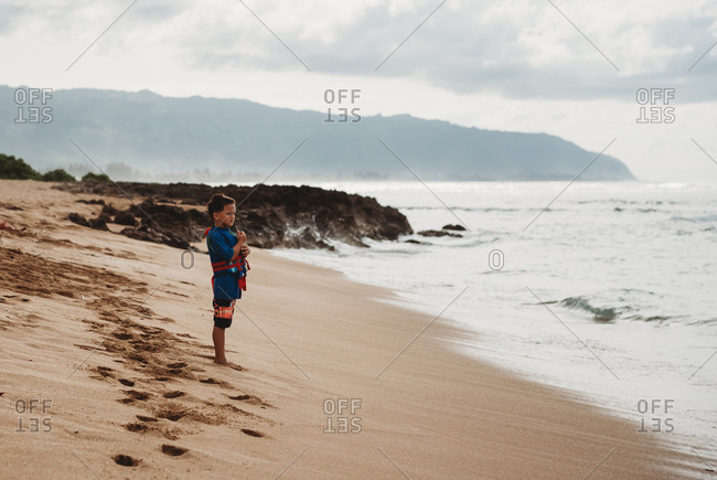 Young boy wearing life vest standing on beach in Oahu, Hawaii