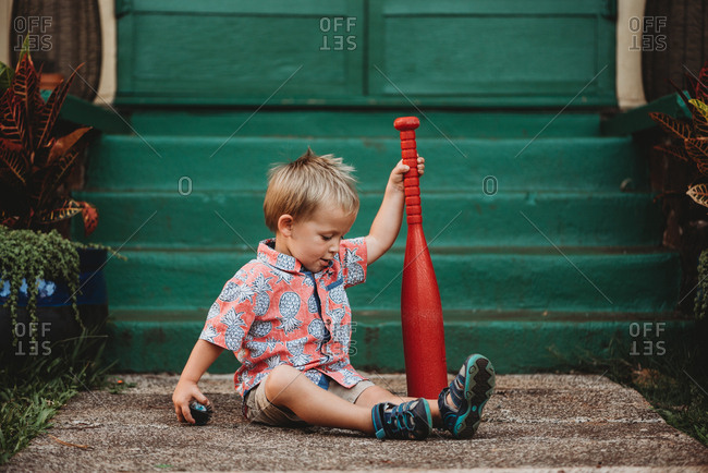 Toddler boy sitting and holding a red plastic bat