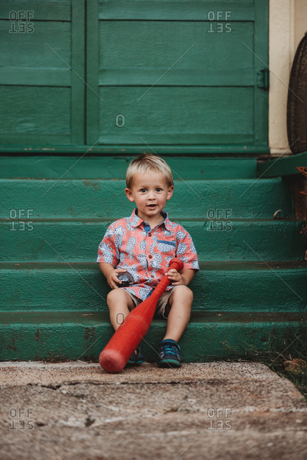 Happy toddler boy holding a red plastic bat