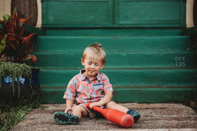 Happy toddler boy with eyes closed holding a red plastic bat