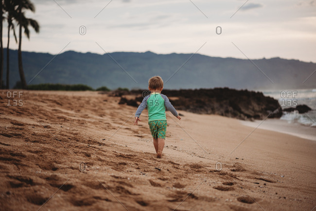 Rear view of toddler boy walking on sandy beach