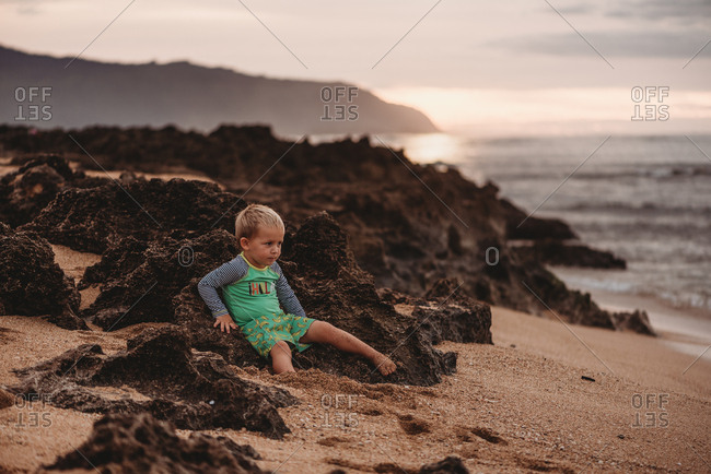 Toddler boy sitting on Hawaii beach at sunset