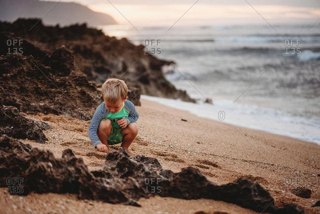 Toddler boy playing on Hawaii beach at sunset