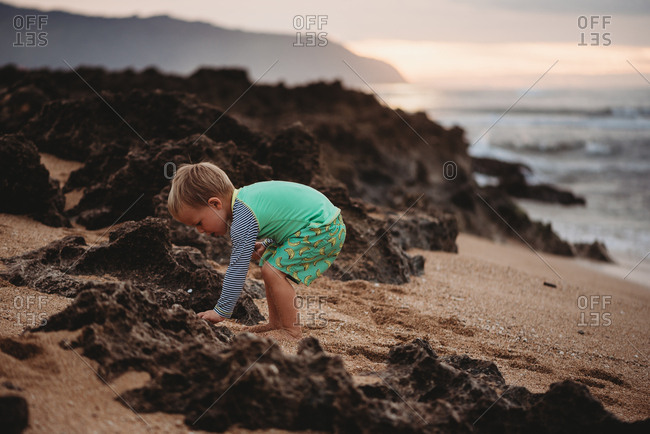 Toddler boy playing in the sand on Hawaii beach at sunset