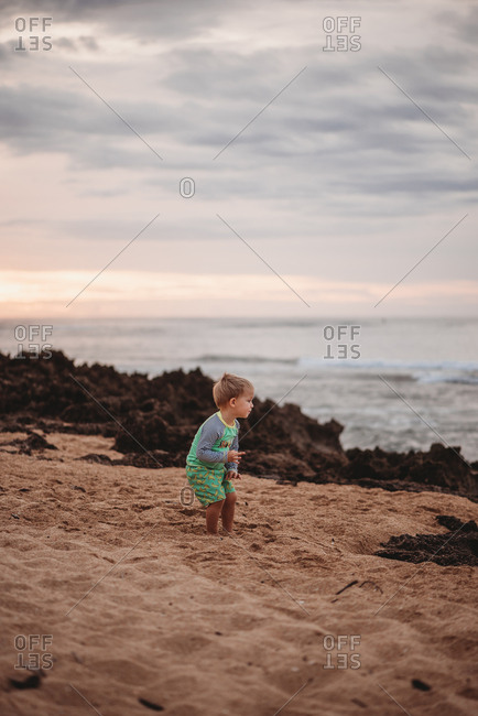 Toddler boy playing in the sand on a beach at sunset
