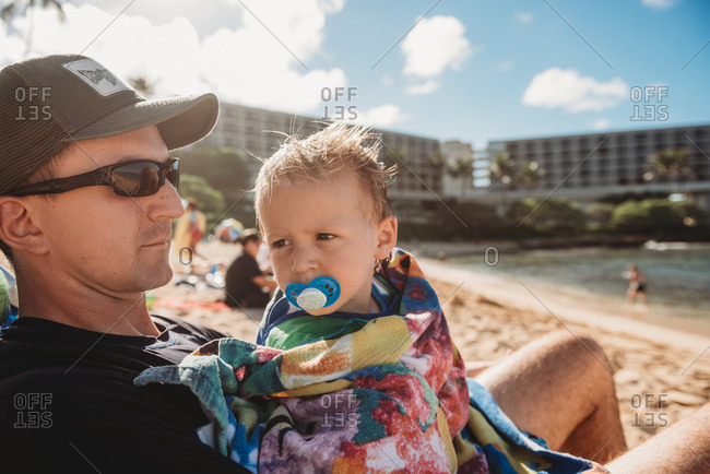 Father and son on a sitting on beach in Hawaii