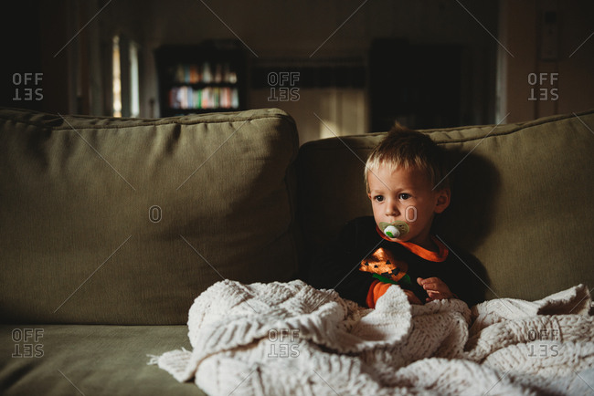 Toddler boy sitting on sofa with blanket