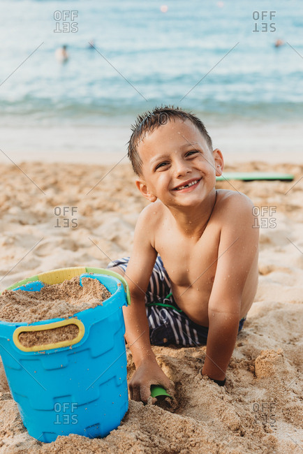 Happy boy playing in the sand on a beach at sunset