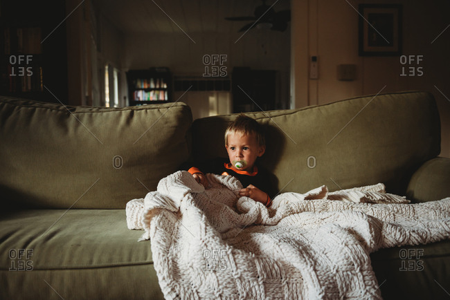 Toddler boy resting on sofa with blanket