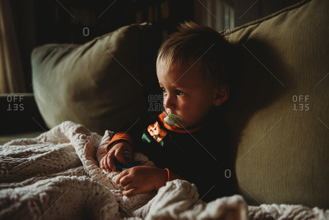 Toddler boy sitting on sofa with blanket and pacifiers