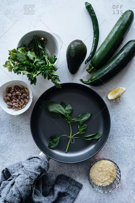 Fresh vegetables and herbs beside pan