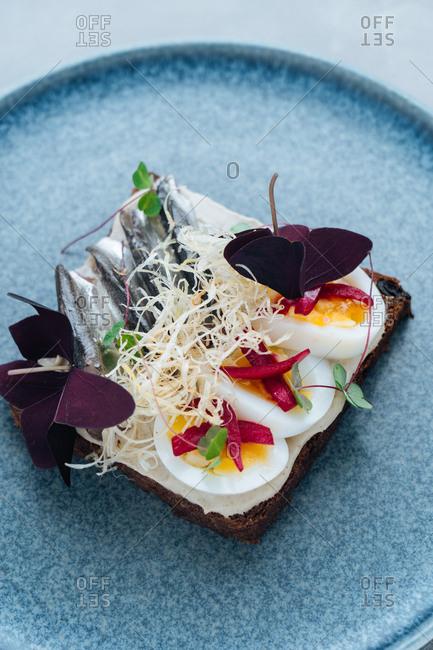 Gourmet sardine dish on a blue plate