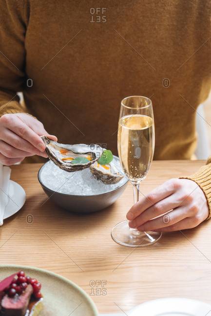 Person eating oysters and drinking champagne