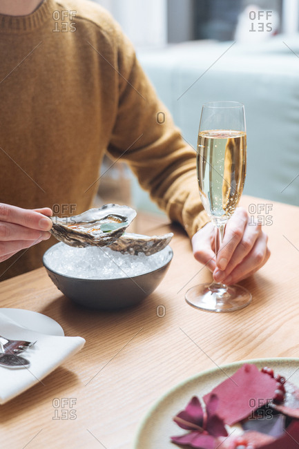 Man eating oysters and drinking champagne